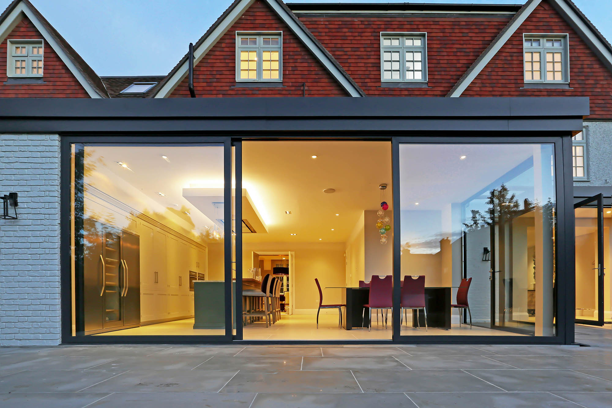 Exterior view of completed Putney period home extension with glass doors looking into large open plan kitchen