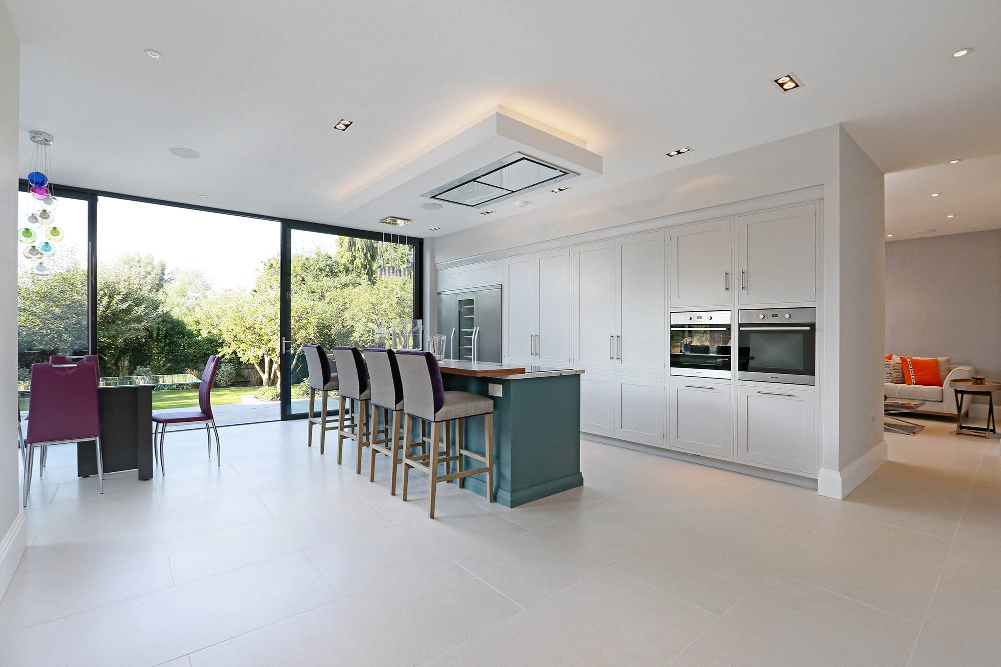 Interior of completed white spacious open-plan kitchen extension for Putney home restoration project