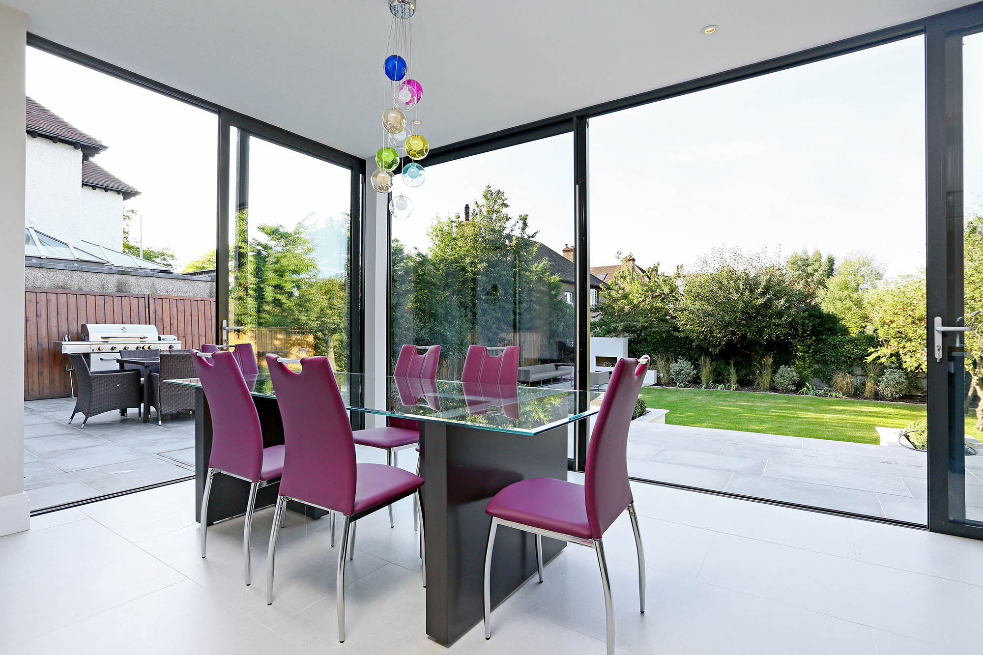 Completed extension for Putney home renovation with dining area and floor-to-ceiling glass walls leading out into the garden