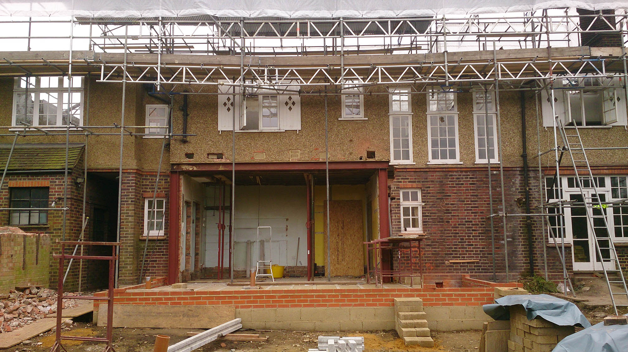 Putney Restoration project exterior work in progress photo of the rear of the house with scaffolding and extension walls.