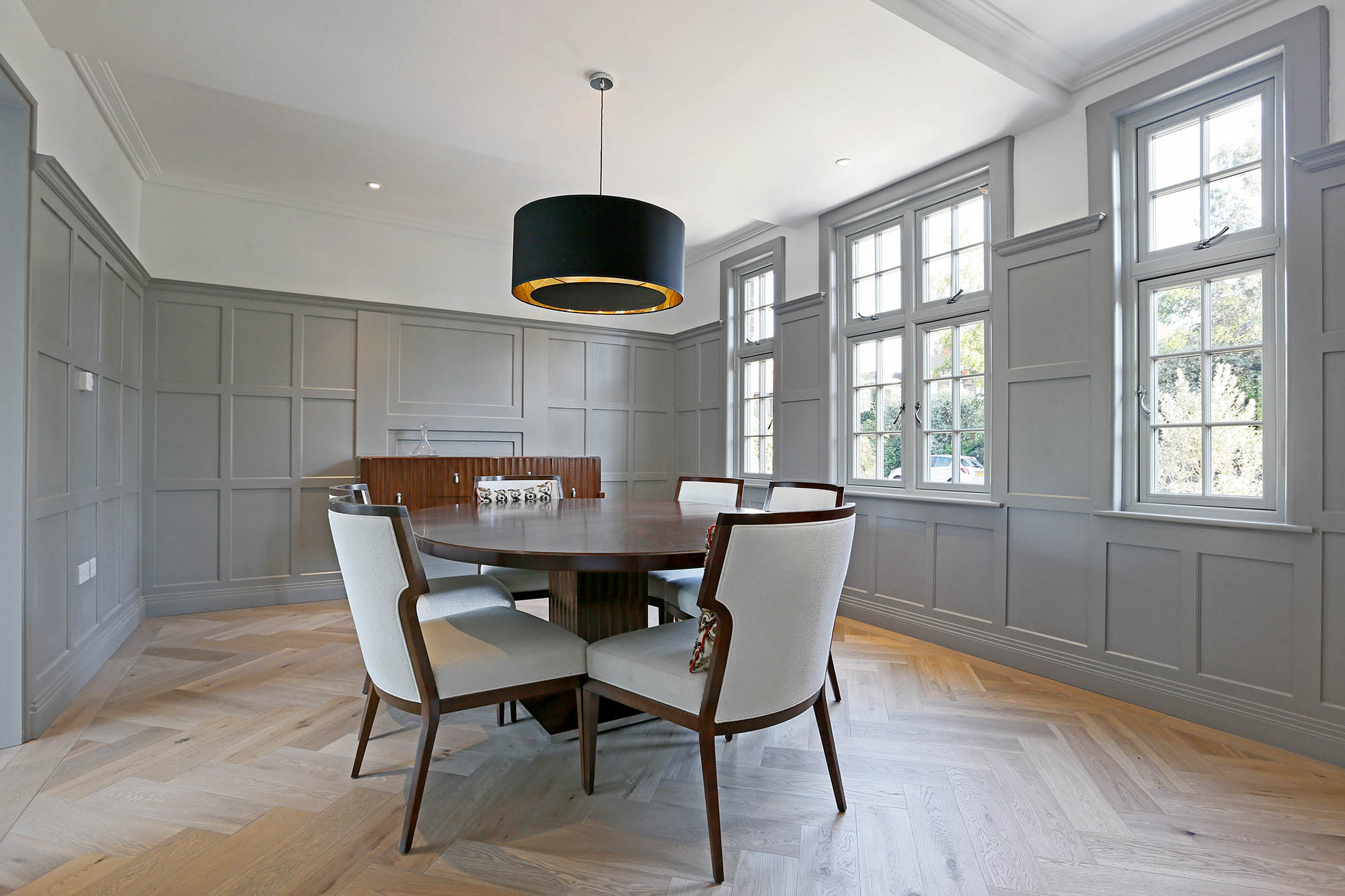 Formal dining room for Putney home restoration project with grey panelled walls and parquet flooring.