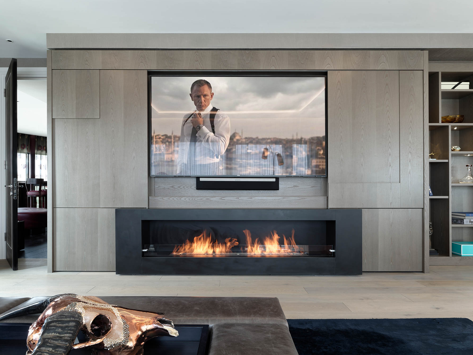 Completed Lounge area for Luxury Penthouse with letterbox fireplace and media wall doors open displaying widescreen television showing James Bond.