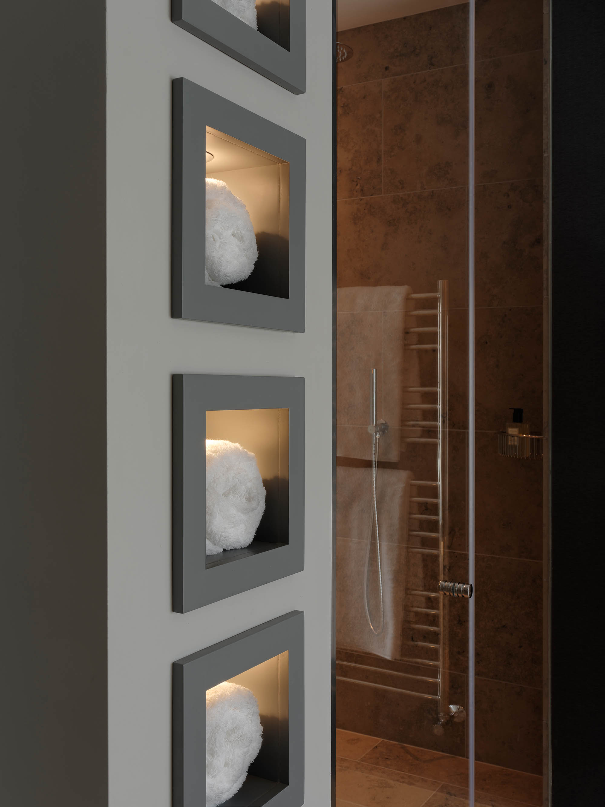 Bathroom / shower room design with towel shelves built into the wall