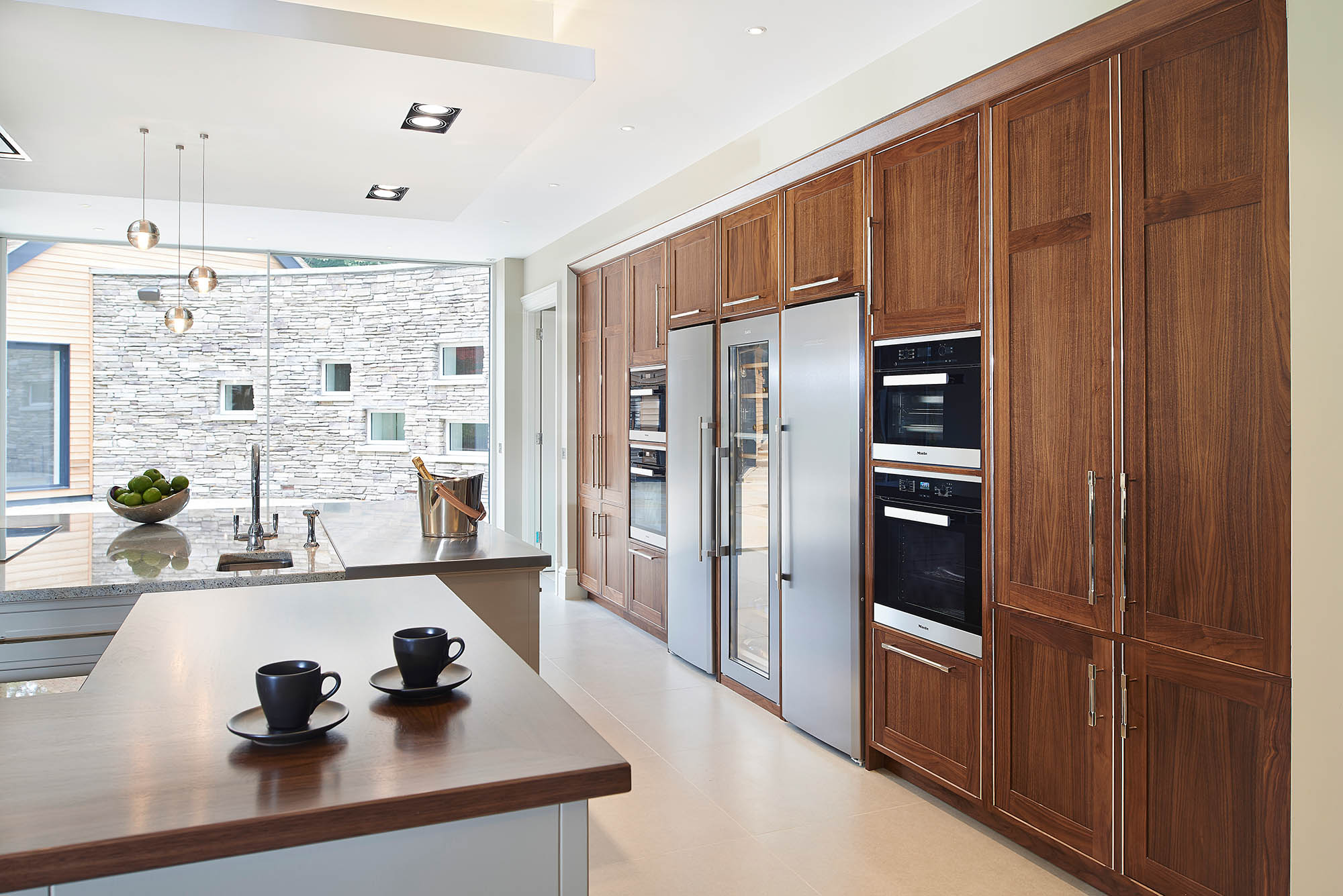 Large modern open plan David Linley kitchen design in American Walnut for Luxury Coombe Estate Home