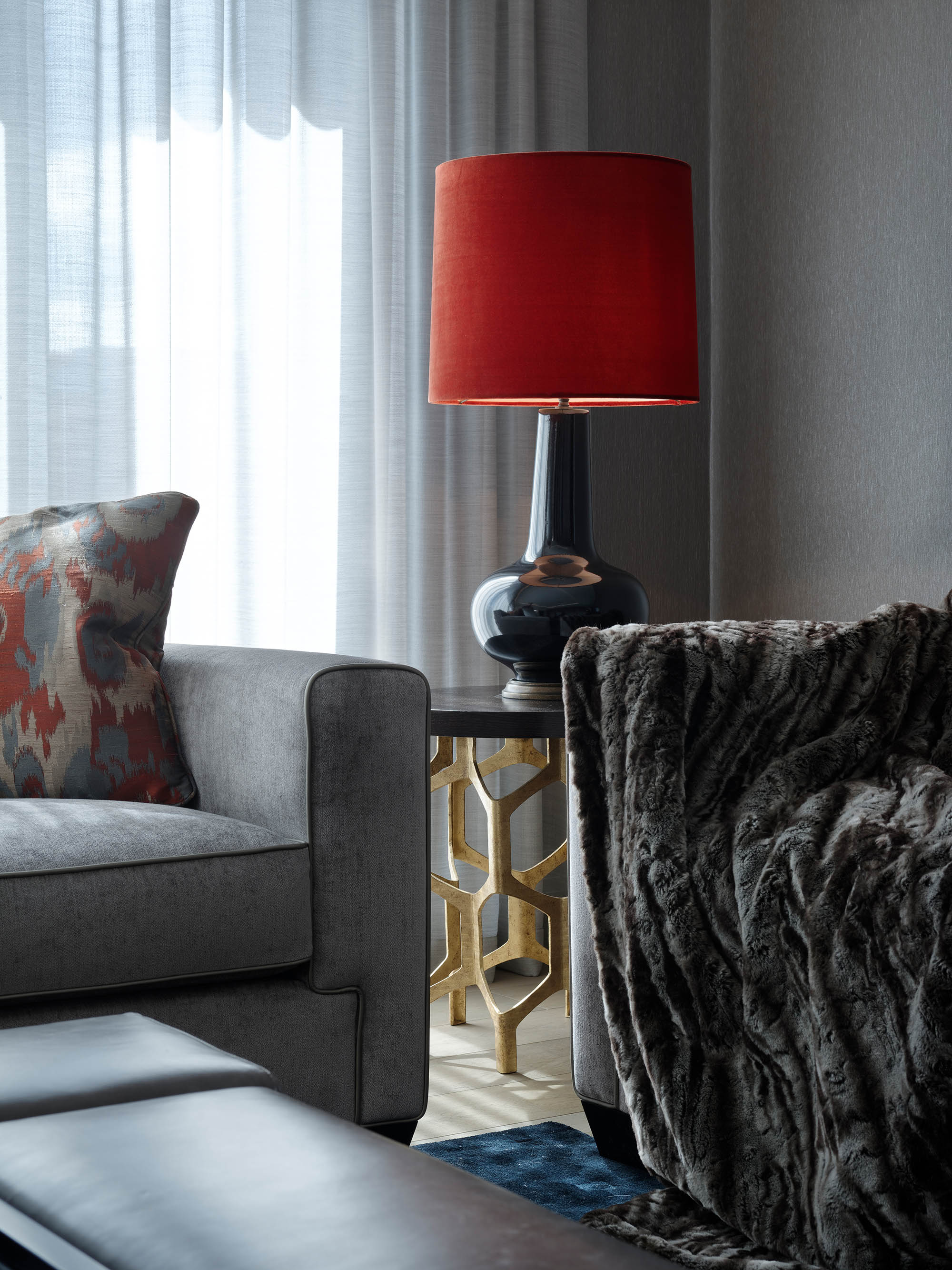 Luxury design details from the sitting room of the Chelsea penthouse renovation: sofas, cushion, lamp. side table and faux fur throw