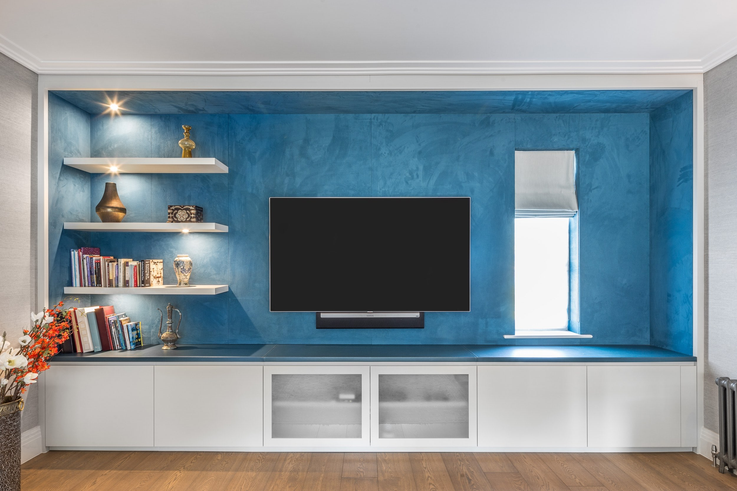 Blue and white recessed media wall with display shelving and storage cabinets