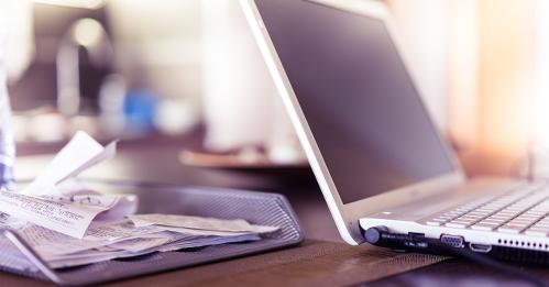 Computer am Schreibtisch mit Belegen für die Steuererklärung
