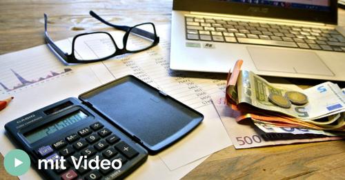 Schreibtisch mit Computer, Taschenrechner und Geld