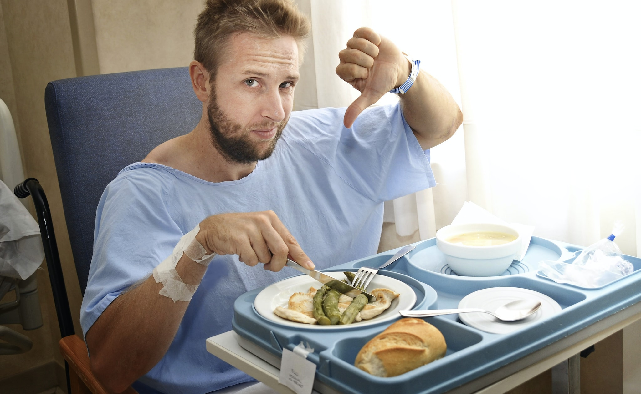 A man in hospital gives his meal a thumbs-down