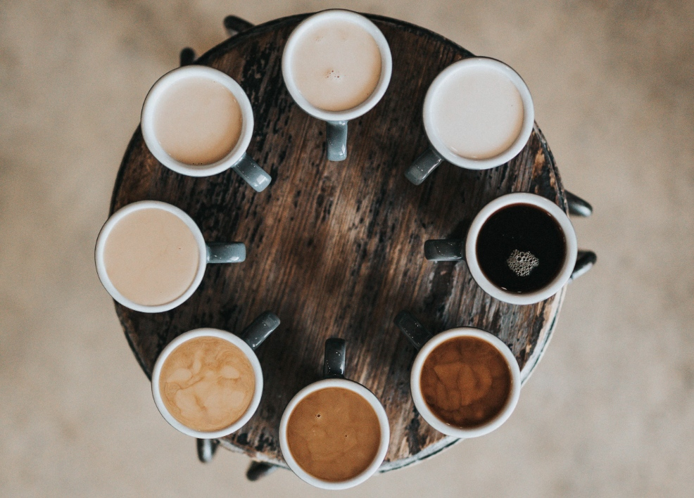 Cups of coffee with milk in them on a round table