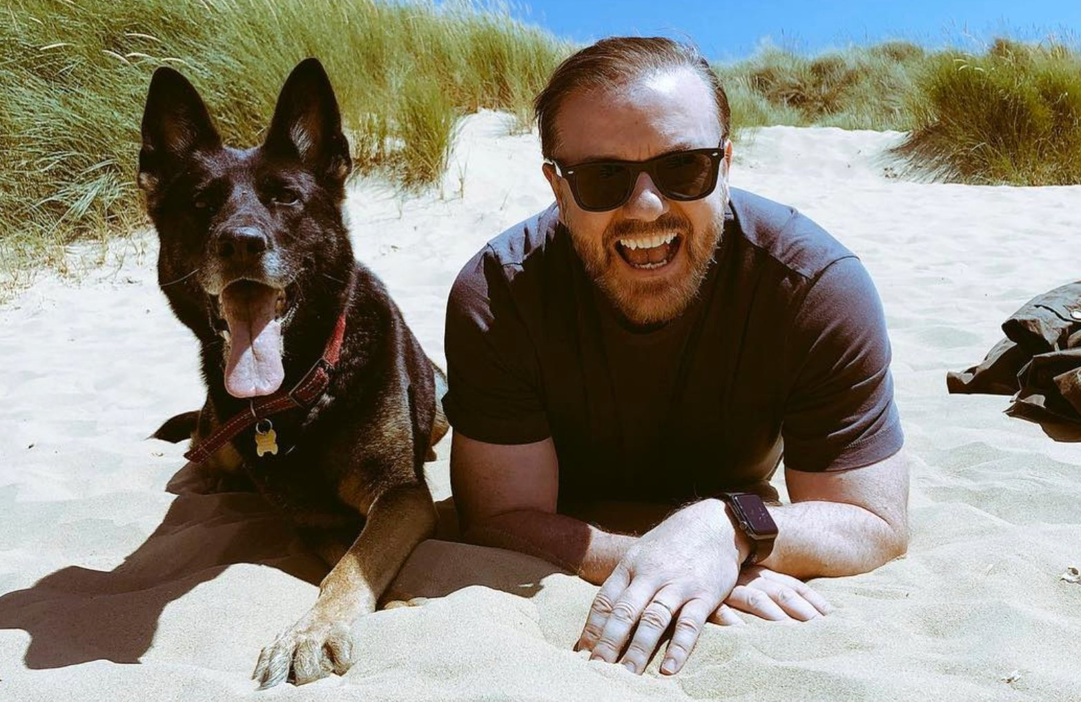 Comedian Ricky Gervais sits on the beach with a dog