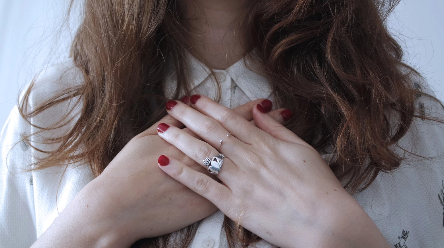 A young woman crosses her hands over her heart