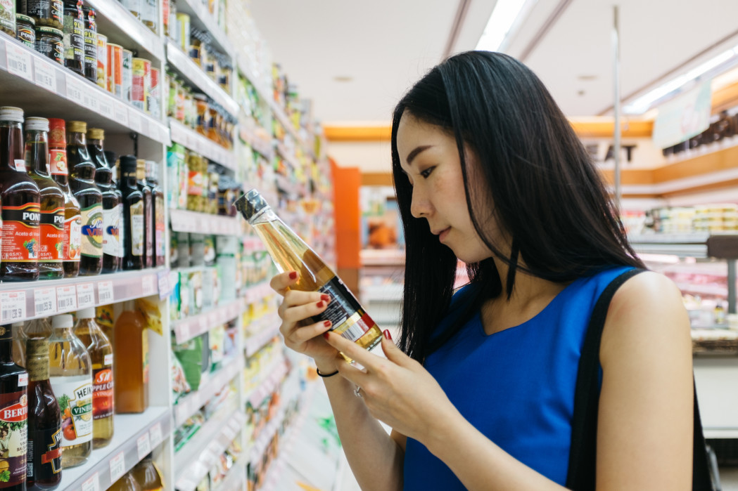 A young woman looks at a product while shopping in the supermarket