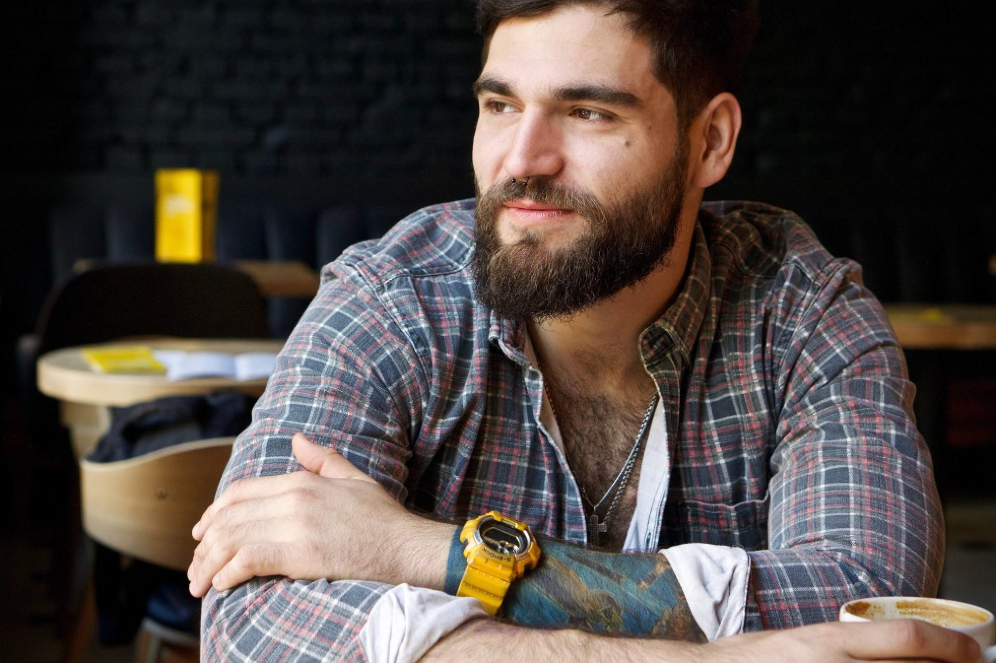 A tattooed man sits in a cafe drinking coffee