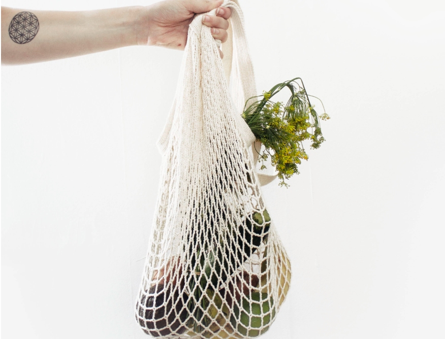 A tattooed arm holds a string bag of vegetables. Zero waste.