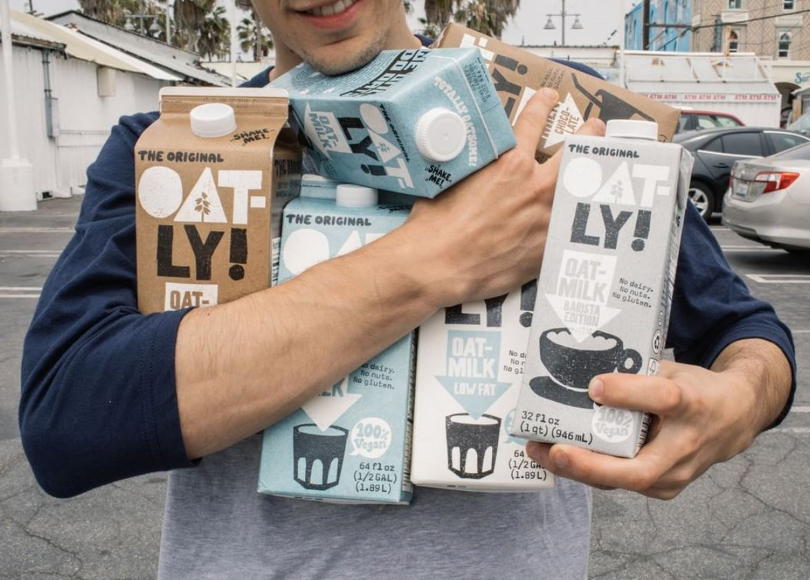 Man holding Oatly vegan milk cartons