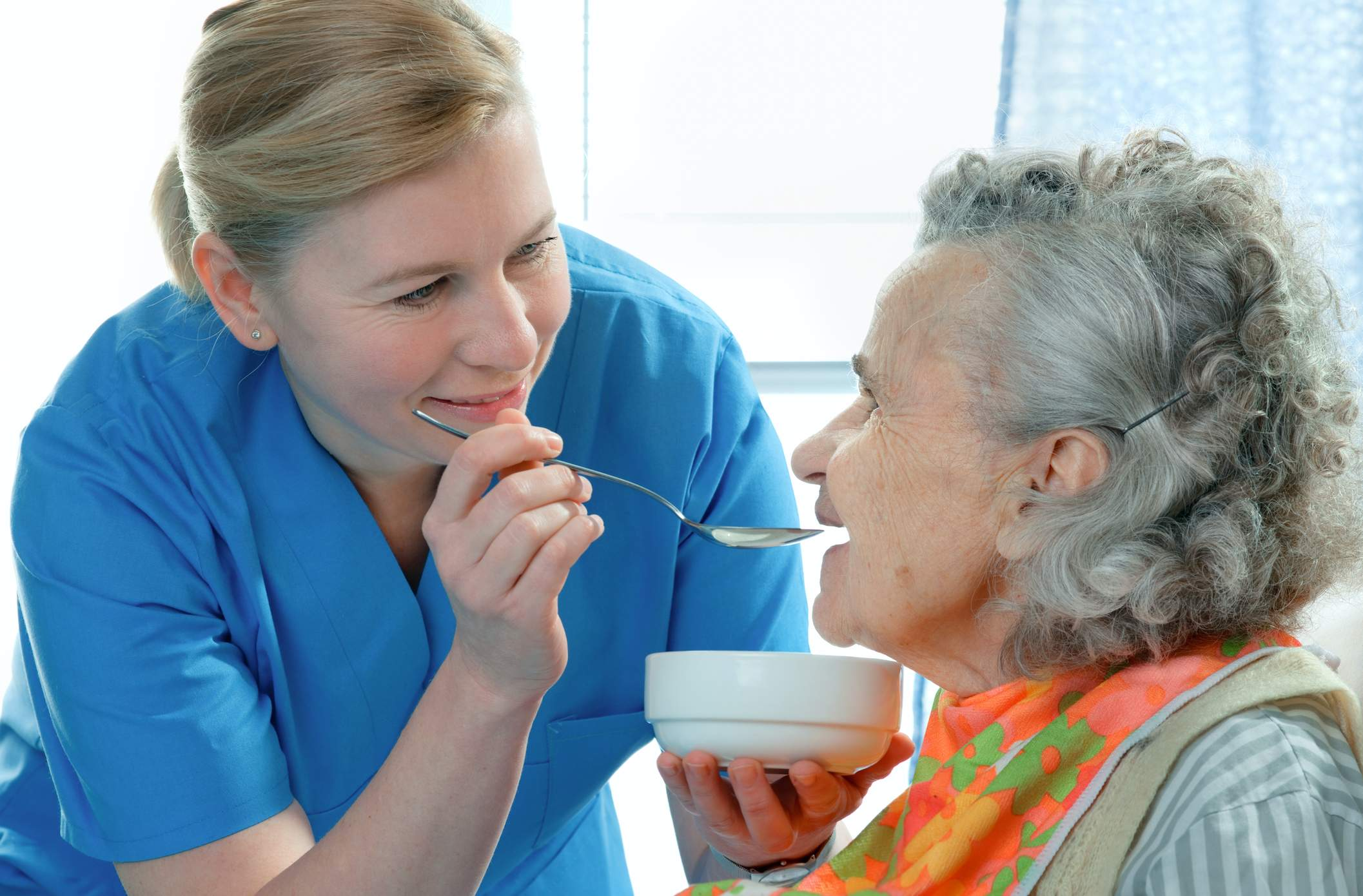 A nurse feeds soup to an elderly patient