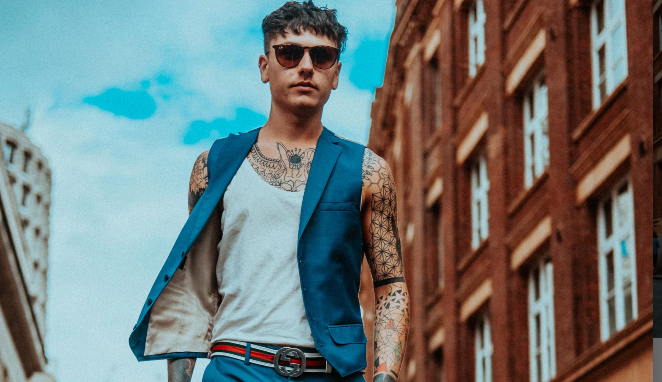 A tattooed man in a suit