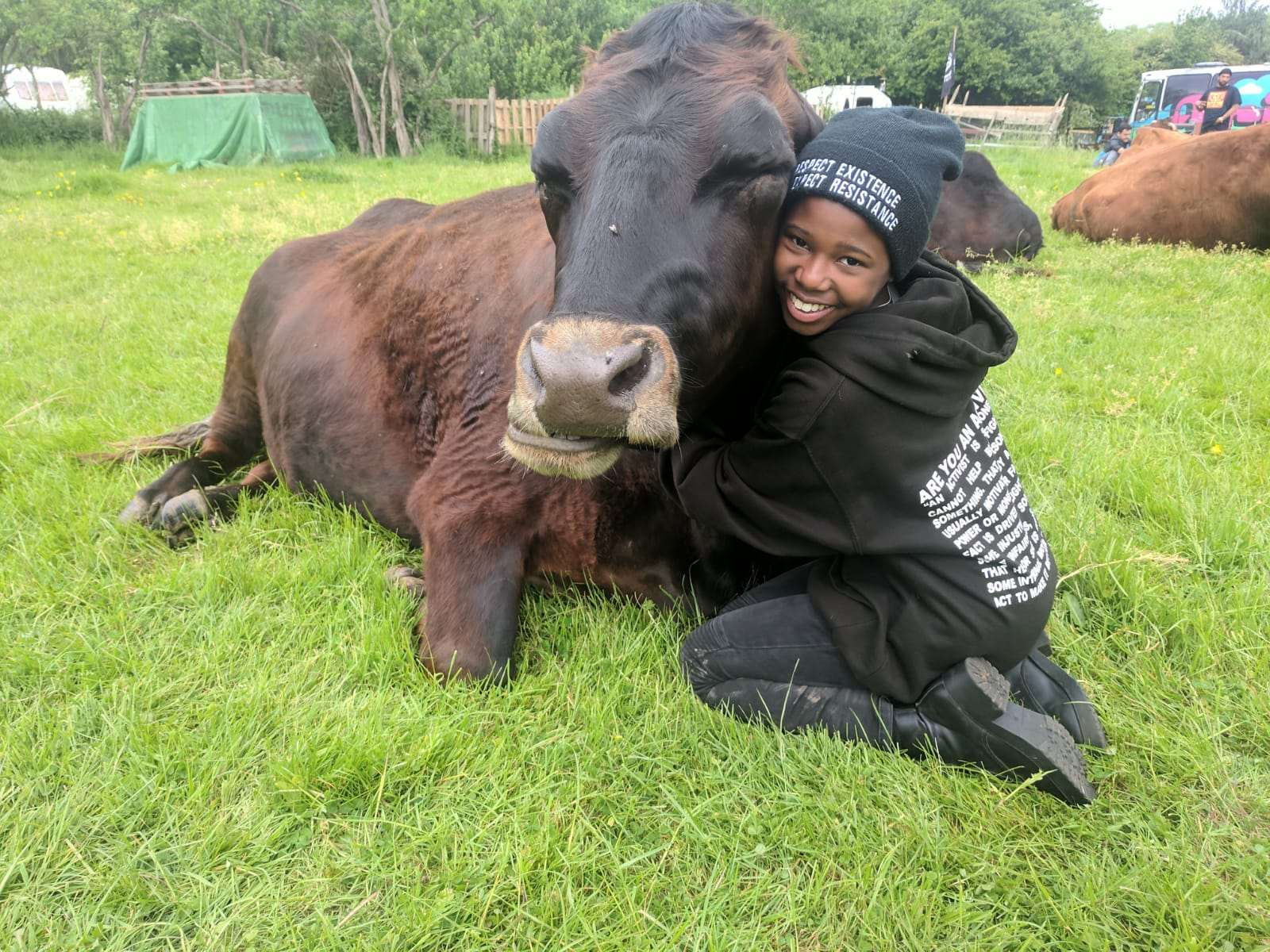 Vegan activist Aiyana Good fellow hugs a cow