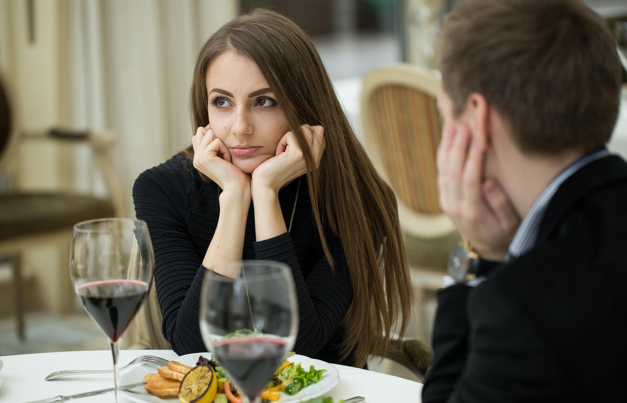 A man and woman eat together looking sad