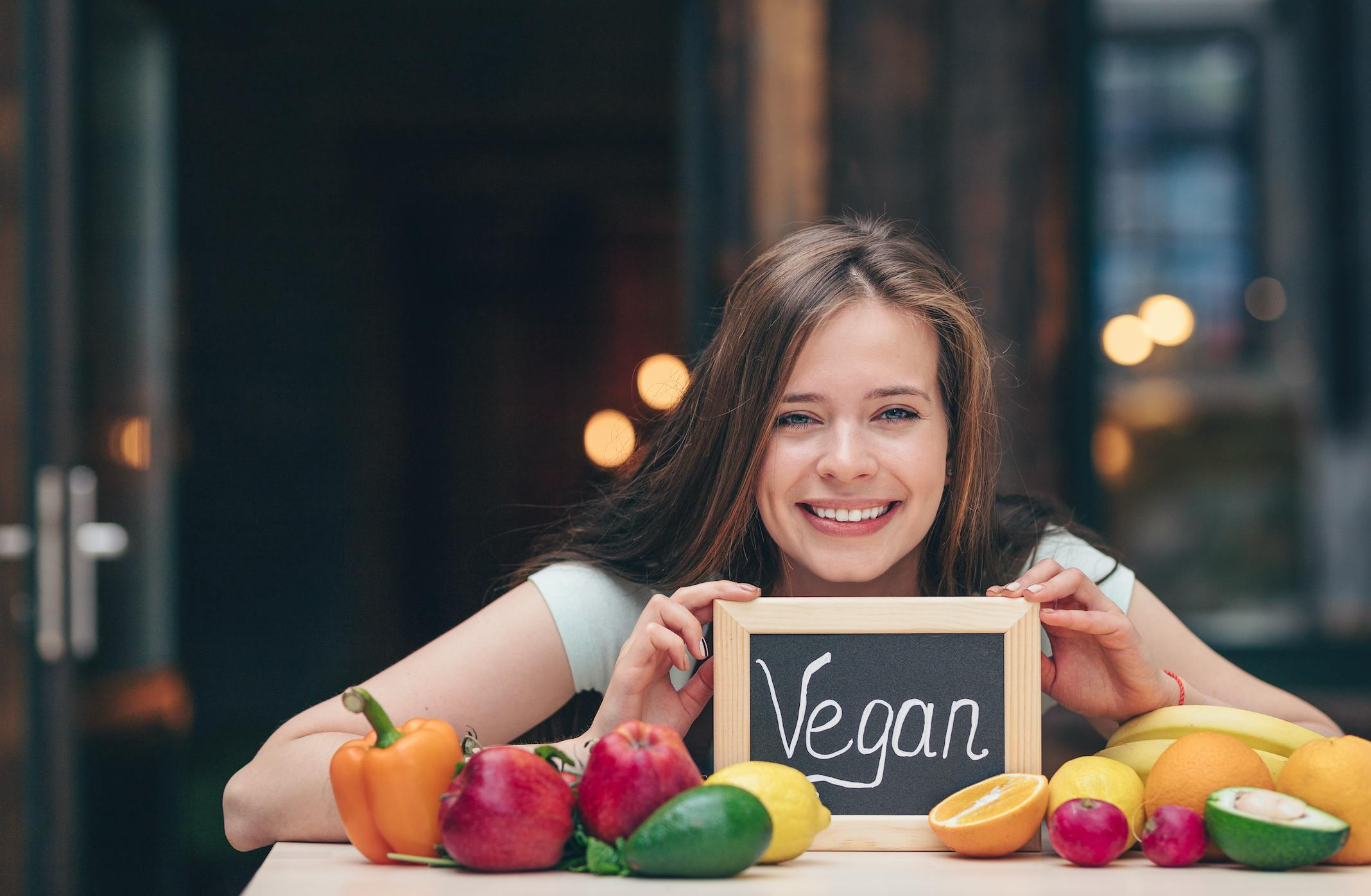 Vegan woman sits next to vegetables