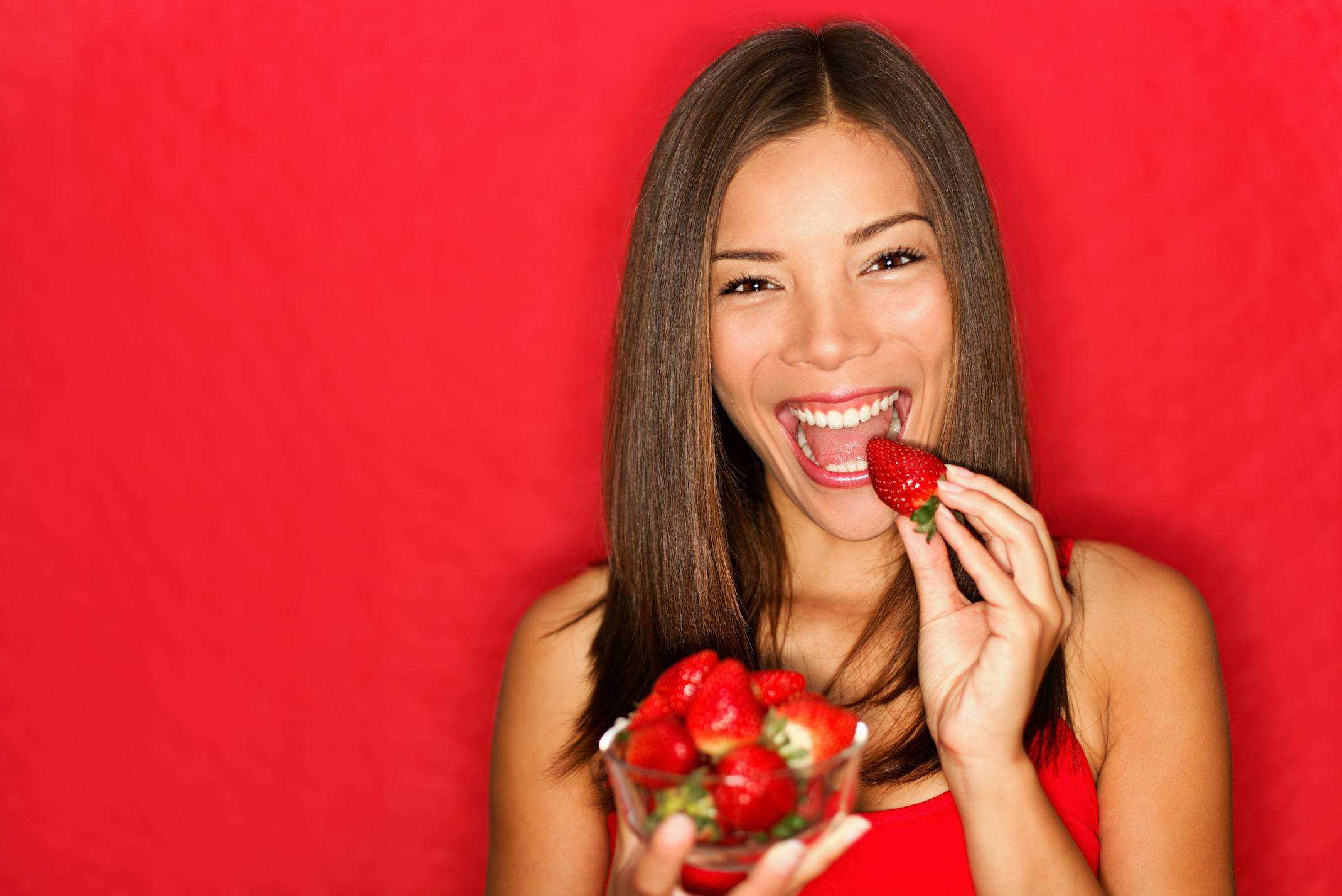 A woman eating strawberries