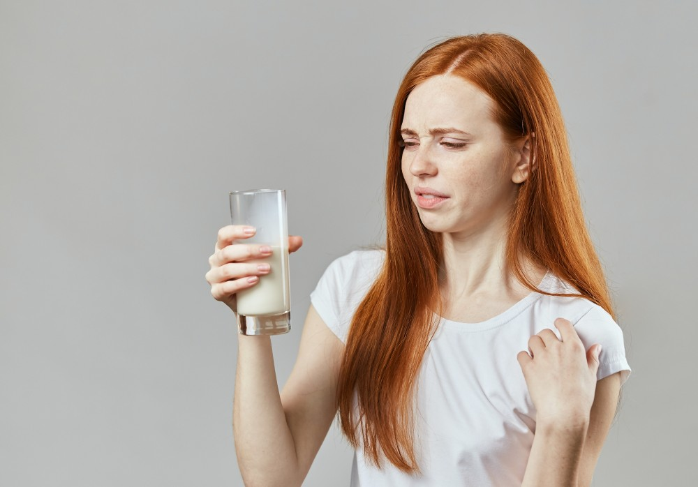 Girl looks disgusted at a glass of milk