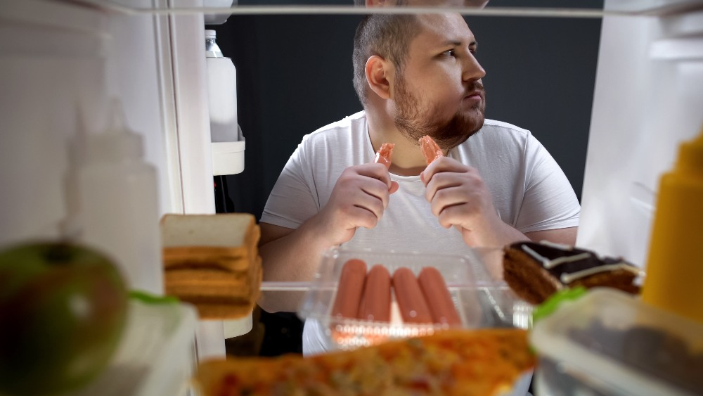 Man sneaking sausages out of the fridge
