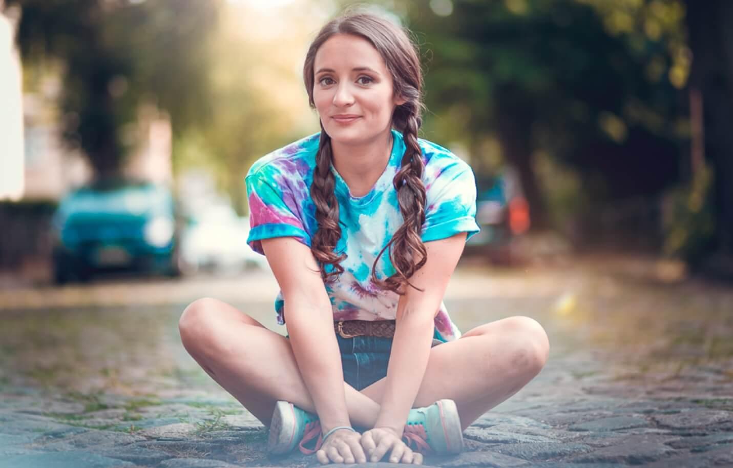 Anna sitzt mit gekreuzten Beinen.