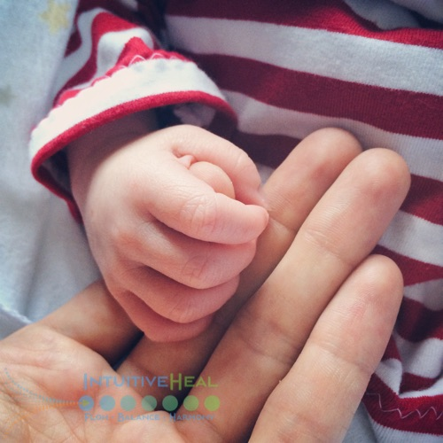 Photo of baby grasping an adult's finger
