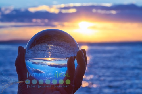 Photo of crystal ball looking through seascape and sunset