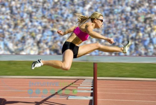 Photo of a woman going over a hurdle