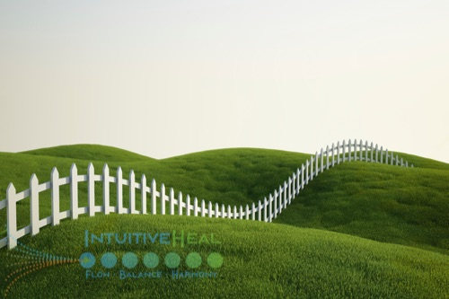 Photo of a white picket fence over rolling hills