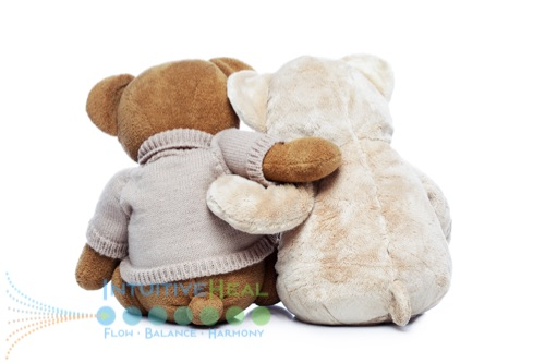 Photo of the back of two stuffed bears arm in arm