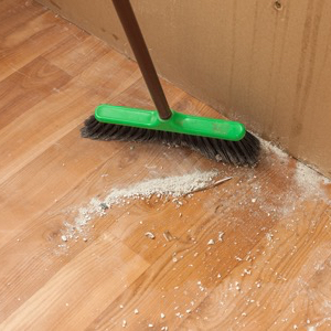 Sweeping debris clean after a renovation project.