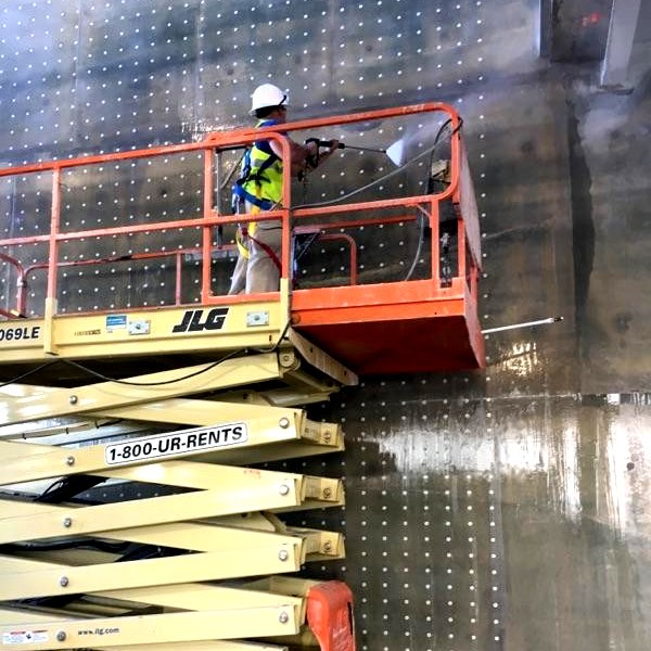 Commercial building walls being pressure washed clean.