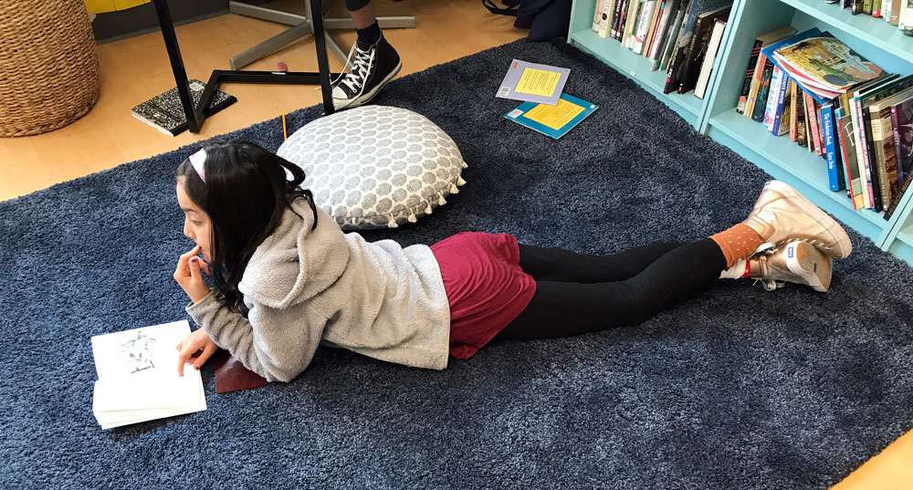 Our classrooms are designed as flexible learning spaces where students can use designated areas to complete projects. Here a student works independently to complete an assignment in the reading nook.