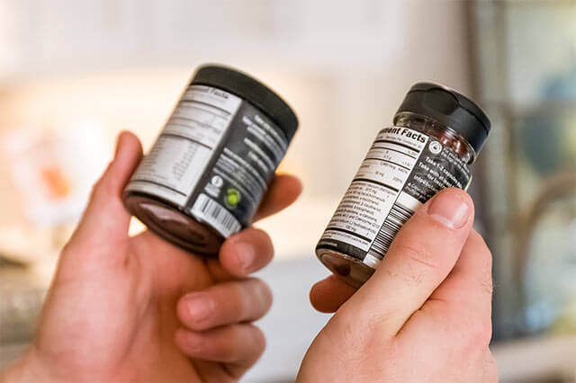 Man comparing the old and new Palm Fruit supplement facts