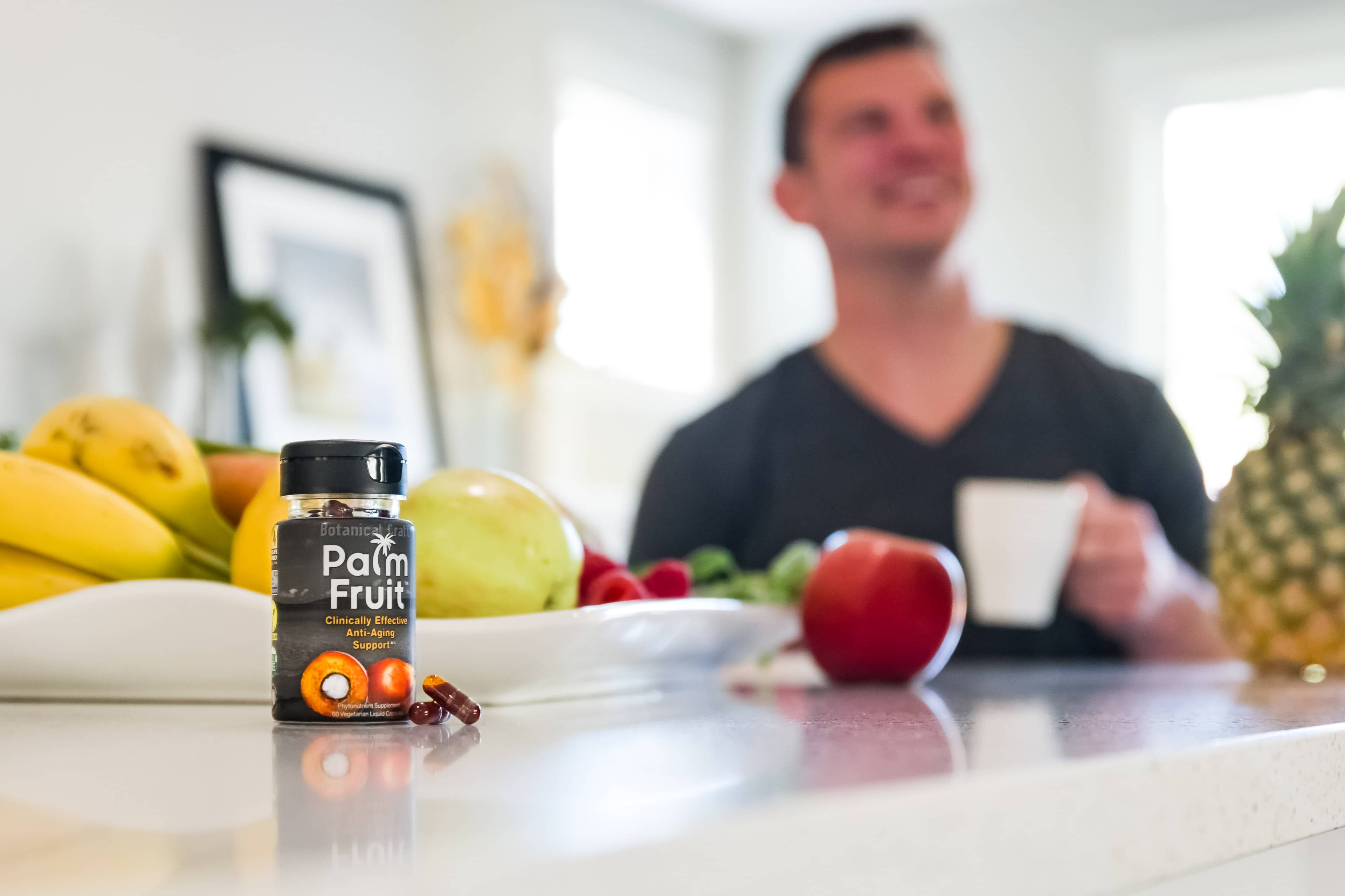 Palm Fruit bottle and liquid capsules sitting on counter top next to plate of fruit.