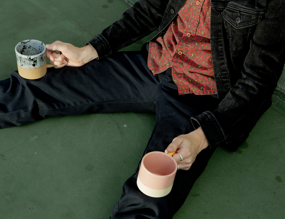 Photo of Alex Oskie with two handmade Loon Ceramics mugs
