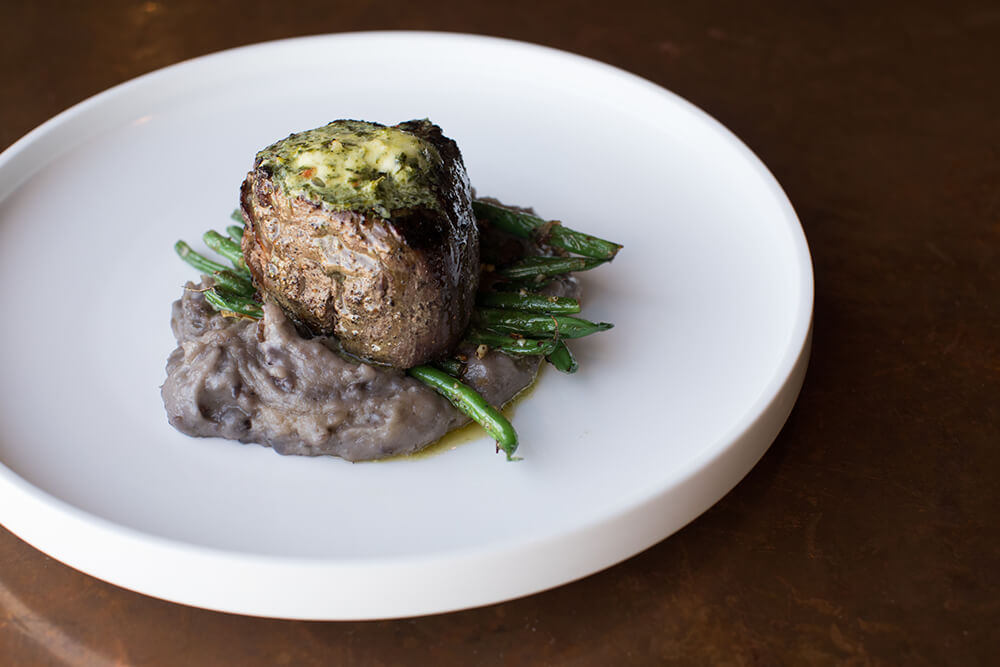 Juniper's succulent, 10-ounce grilled tenderloin, smothered in chimichurri butter sauce, is one of the best steak experiences you can have in Tulsa. (Photo: Valerie Grant)