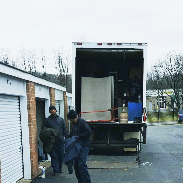 2 men packing moving truck outside of a storage unit