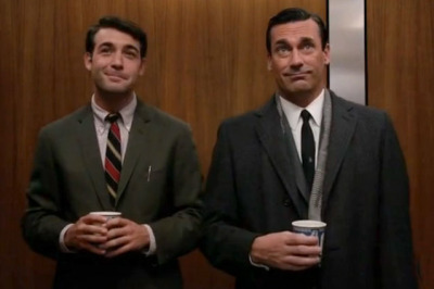 Don draper on an elevator with a colleague. Both in suits holding coffee and smiling.