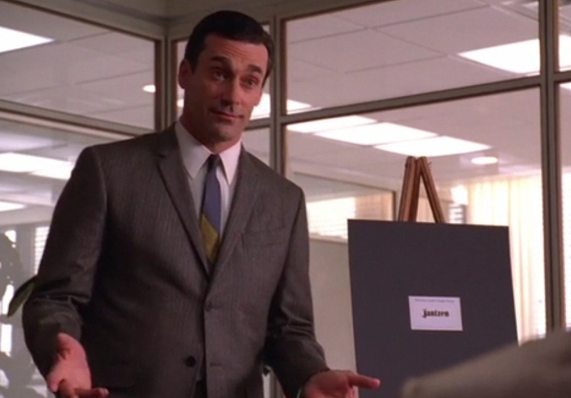 Don Draper in front of an easel with mockups.