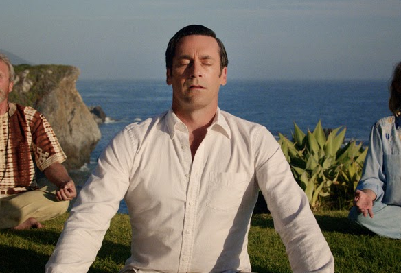 Don Draper meditating on a grassy lawn with the ocean in the background.