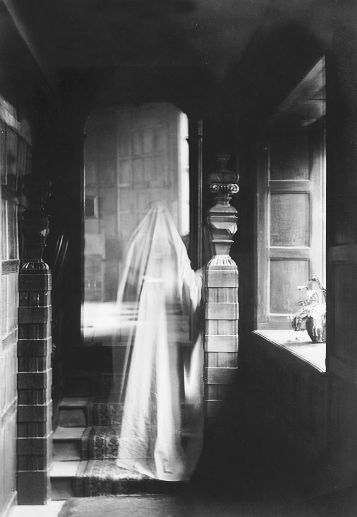 Black and white image of a transparent figure walking up the stairs.