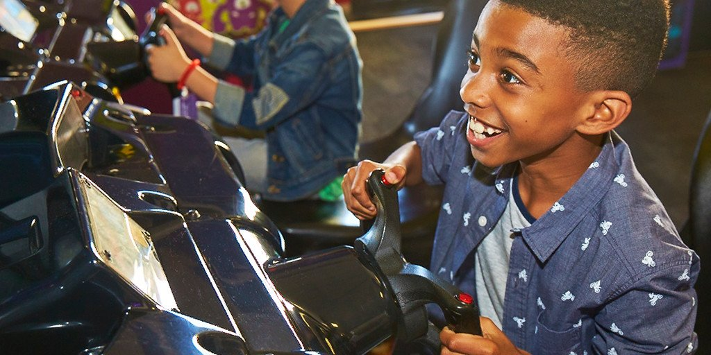 young boy playing an arcade game