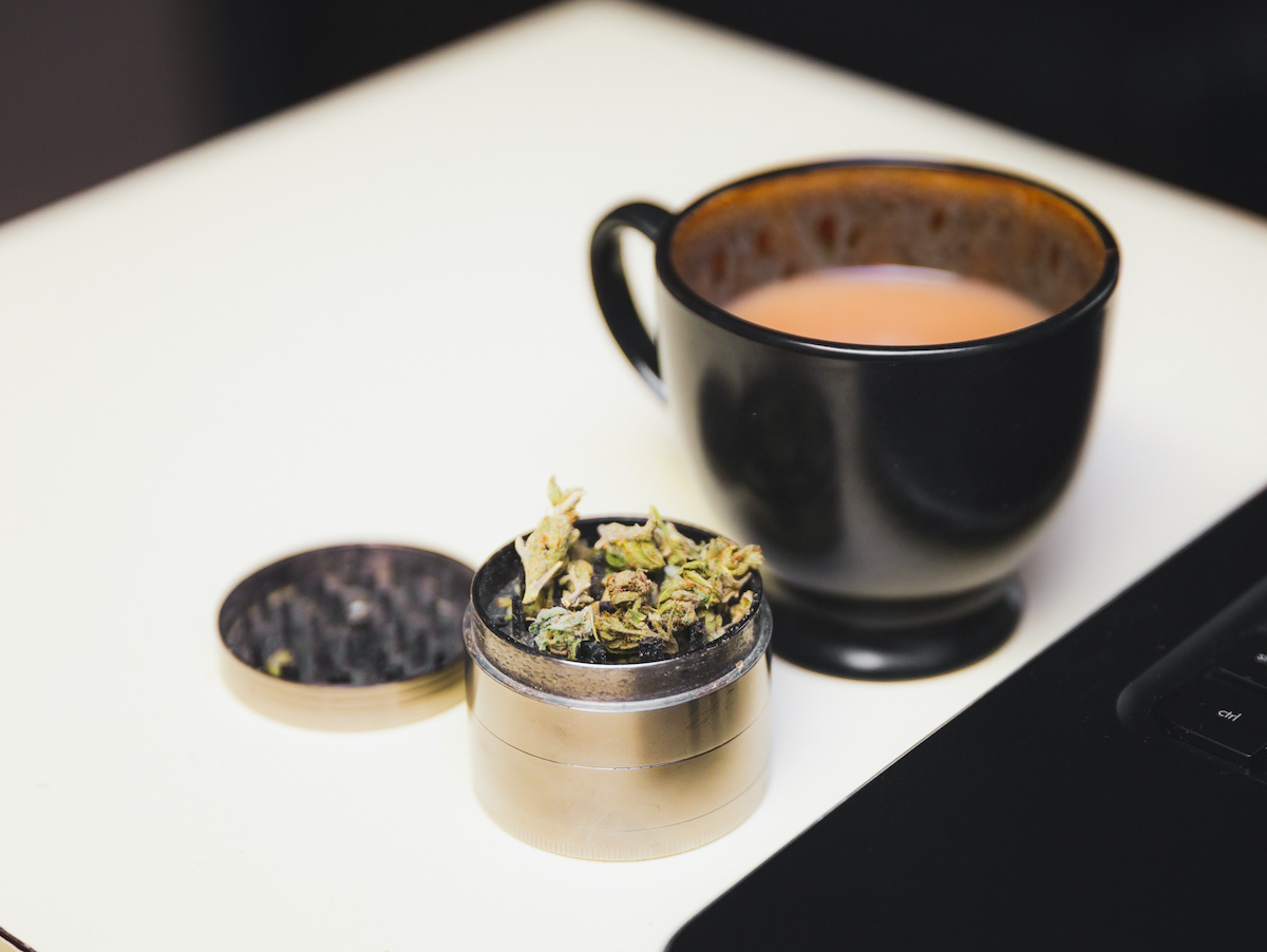 cannabis flower in grinder next to cup of coffee