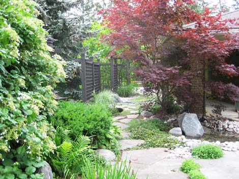 A perfectly blended garden design featuring stone, pebbles and water - this used to be an asphalt drive
