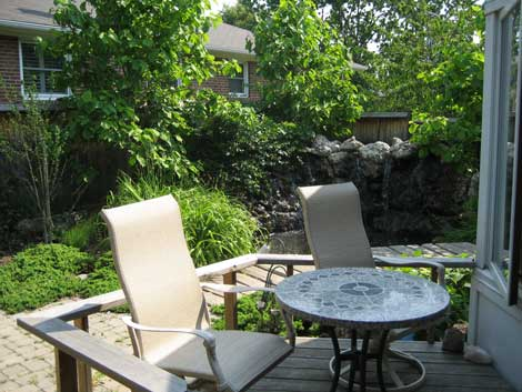 After: the garden transformed with waterfall and lagoon, plus seating and dining patio